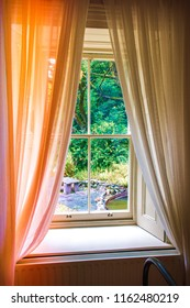Antique style window with delicate white curtains
