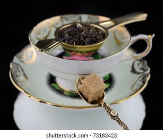 Antique Tea Cup, Spoon & Sugar On Black Background