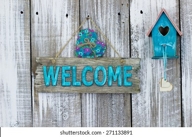 Antique teal blue welcome sign with heart by birdhouse hanging on white painted weathered wood fence