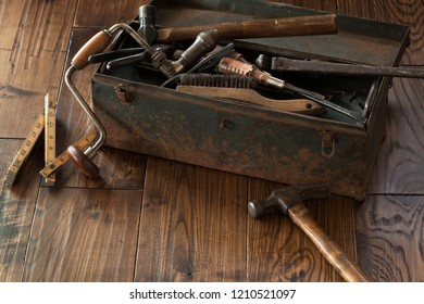 Antique tools and grungy toolbox on dark wood surface