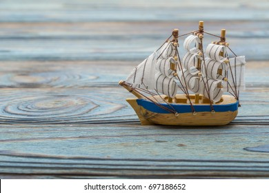 Antique toy sailer. On a blue wooden background replacing the sea, copy space. Marine guide, cruise, travel, postcard.