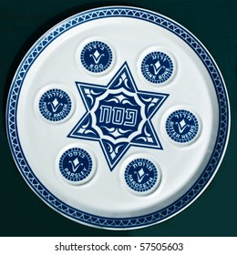 Antique traditional decorative plate for passover seder. Blue star of David and 6 blue circles on white ceramic dish. Isolated on dark background.Jerusalem flea market.