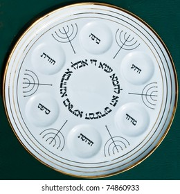 Antique traditional decorative plate for passover seder. 6  images of menorah, 6 white circles and black hebrew letters on white ceramic dish. Isolated on dark background.Jerusalem flea market.