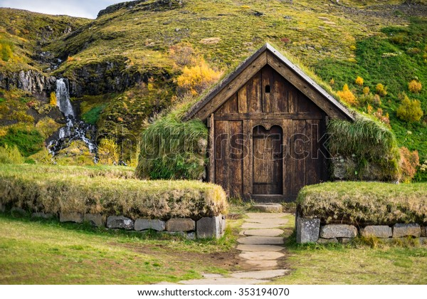 Antique traditional icelandic torf viking house near waterfall