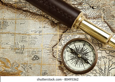 Antique traveling equipment: brass spyglass and compass at old m