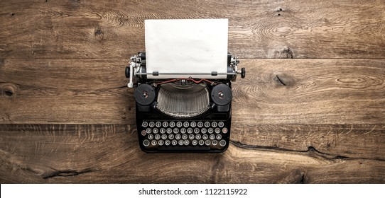 Antique typewriter with grungy textured paper page on rustic wooden background