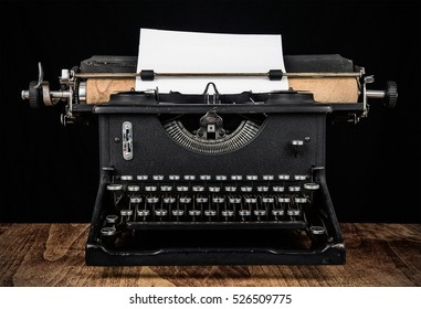 Antique typewriter. An old vintage typewriter on a wooden desk with a black background