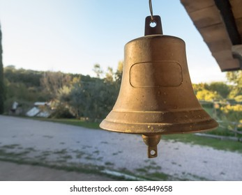Antique unique marine bell hangs from the roof of a farm house, in Italy.