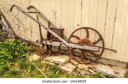 Antique vintage garden plow against a cream colored barn