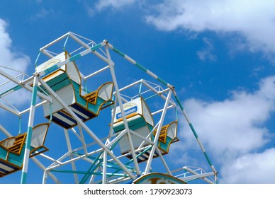 antique vintage old style Ferris wheel closeup detail with wooden gondolas and light white steel frame. blue sky and white clouds. abstract low angle view. yellow and blue striped paint. retro mood.