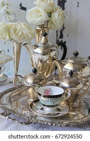 Antique vintage silver tea and coffee set on a silver tray, teacup and saucer, silver vase of roses and silver cutlery flatware