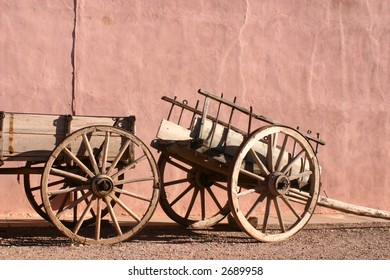 Antique wagon and cart with beige stucco wall background in Tombstone Arizona
