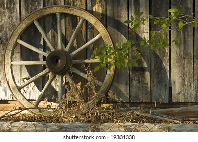 An antique wagon wheel photographed in the warm late afternoon sun which casts shadows against the barn.