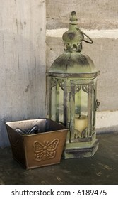 Antique and well used lantern, beside butterfly candle box in front of squared log wall.