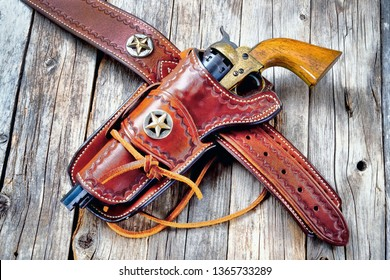 Antique western cowboy pistol in leather holster.