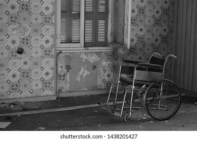 Antique wheelchair in abandoned house interior. Black and white.