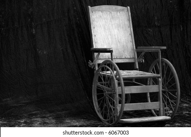 an antique wheelchair in black and white