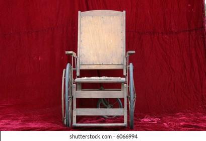 an antique wheelchair seen against red velvet