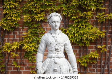 Antique white female statue with green and yellow ivy leaves on a red brick wall in the background. Street scene by the canal in Copenhagen, Denmark.