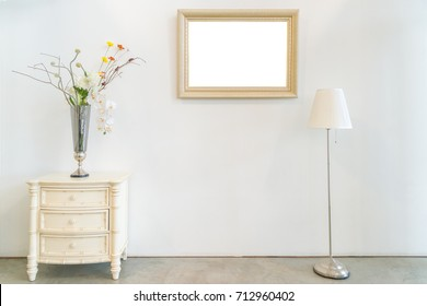 The antique white wooden cabinet, standing lamp and flower vase with vintage photo frame interior decoration