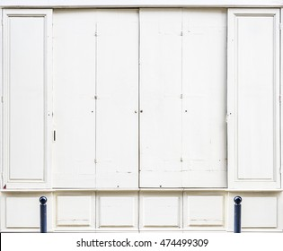 Antique white wooden doors of a store with a number 72 in both sides. Antique european style.
