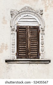 Antique window with closed wooden shutters and stone ornament