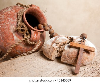 Antique wine jug, cross and rustic loaf of bread as christian symbols of faith