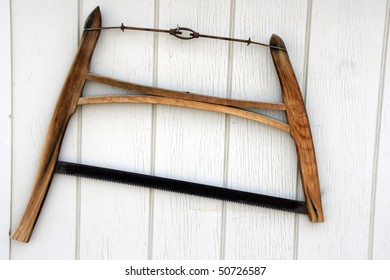 Antique wood saw hanging on a wall.