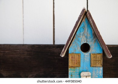 Antique wooden blue bird house with a contrasting white boarded fence in the background.