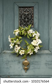 Antique wooden blue door with artificial flower wreath and brass knocker