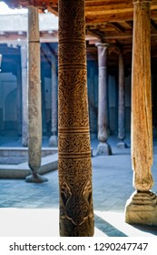 Antique wooden columns with carved ornaments inside the madrasah. Khiva City, Central Asia, Uzbekistan.