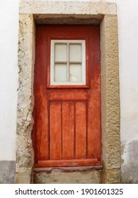an antique wooden door in red color of a house in Europe.