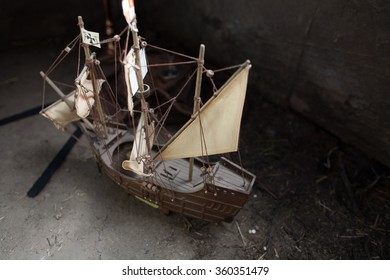 Antique wooden miniature toy reproduction model war sail ship with nostalgic aged canvas sails in an old wood attic lit by diffused dusty light
