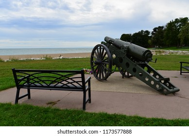 Antique wooden wheeled cannon in Kenosha Wisconsin along the Lake Michigan shoreline pointing south in front of park bench.