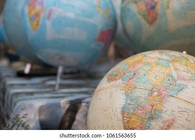 Antique world globes at an outdoor flea market. One tan antique globe in foreground and blue earth globes in the background, shallow depth of field,  Group of globes for sale at outdoor bazaar.