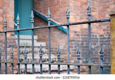 Antique Wrought Iron Fence with Selective Focus. Brick Wall with Doorway and Staircase in  the Background.