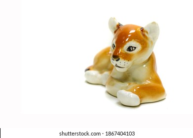 Antiques, art, collectibles. Swap meet. Isolated over white background. figurine of a tiger lying on the floor, glazed ceramics