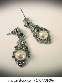 Antique-style faux pearl and silver metal earrings