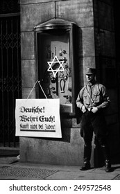 Anti-Semitic boycott Berlin, Germany, April 1, 1933. A Nazi storm trooper stands beside a placard reading, 'Germans, defend yourselves, do not buy from Jews'. It is posted on the Jewish Tietz store.