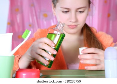 Antiseptic solutions mouthwash in hands girl teen. Standing in the bathroom neutralize bacteria in the oral cavity. Daily hygiene