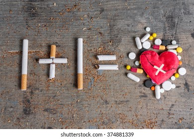 Antismoking background. Diseased heart and pills on wooden surface. Stop smoking now
