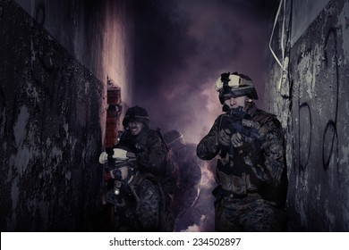 Anti-terrorist operation. Soldiers in full gear. Going up in smoke. Destroyed object.