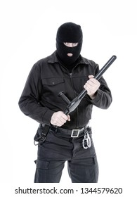 Antiterrorist police guy wearing black uniform and black balaclava holding firmly police club in both hands, shot on white
