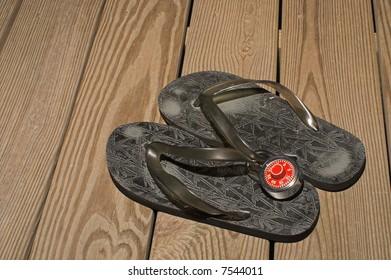 An anti-theft padlock on a pair of flip flops.