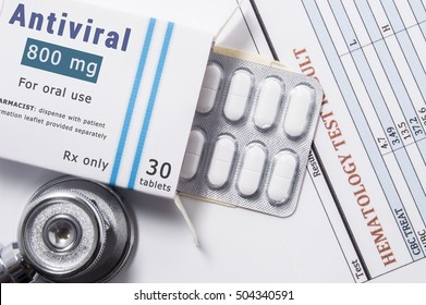 Antiviral drug. Open paper packaging box of medication with name group of drug Antiviral, blister with pills, next to stethoscope and blood test results. Concept for treatment of virus diseases