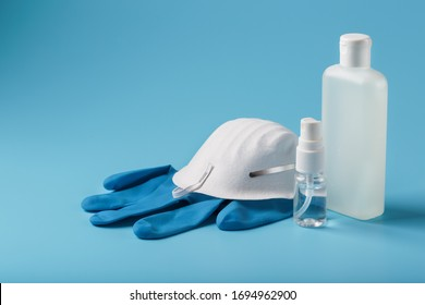 Anti-virus protection kit on a blue background, mask, rubber gloves, hand sanitizer bottles, antiseptic gel.