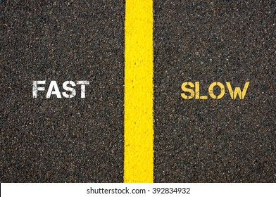 Antonym concept of FAST versus SLOW written over tarmac, road marking yellow paint separating line between words