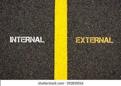 Antonym concept of INTERNAL versus EXTERNAL written over tarmac, road marking yellow paint separating line between words