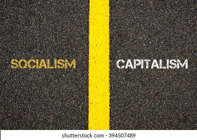Antonym concept of SOCIALISM versus CAPITALISM written over tarmac, road marking yellow paint separating line between words