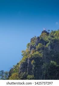 ant's eye view of Pha Chu Thong peak mountain with Thai flag and blue sky background, Pha Chu Camp Site, Sri Nan National Park, Nan, Thailand.